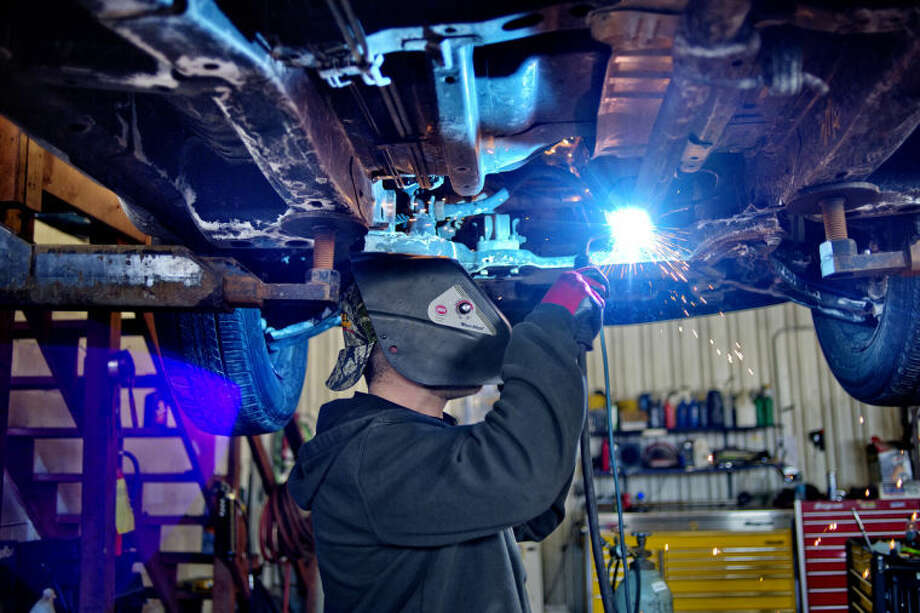 NICK KING   nking@mdn.netEmployee Nathan Hall welds an exhaust while repairing a customer's car at Pickering Automotive Services in Midland. The cold weather has affected the type of repairs seen at the shop as well as Pickering's other operations. Photo: Nick King/Midland  Daily News