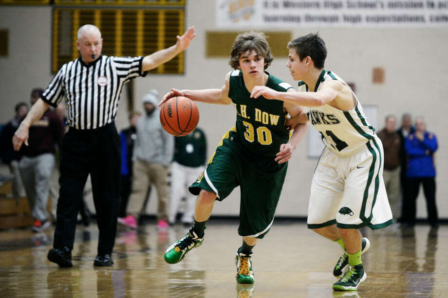 SEAN PROCTOR   sproctor@mdn.netDow's Kyle Cushman dribbles by Saginaw Heritage's Max Modrall Wednesday during their Class A district game at Bay City Western. Dow defeated Saginaw Heritage 66-43. Photo: Sean Proctor/Midland  Daily News