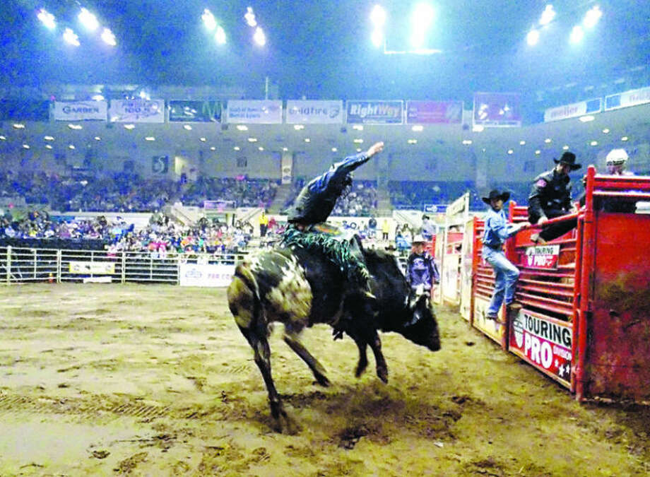 A contestant rides a bull during the Professional Bull Riders event recently at the Dow Event Center in Saginaw. STEPHANIE WIRTZ | for the Daily News