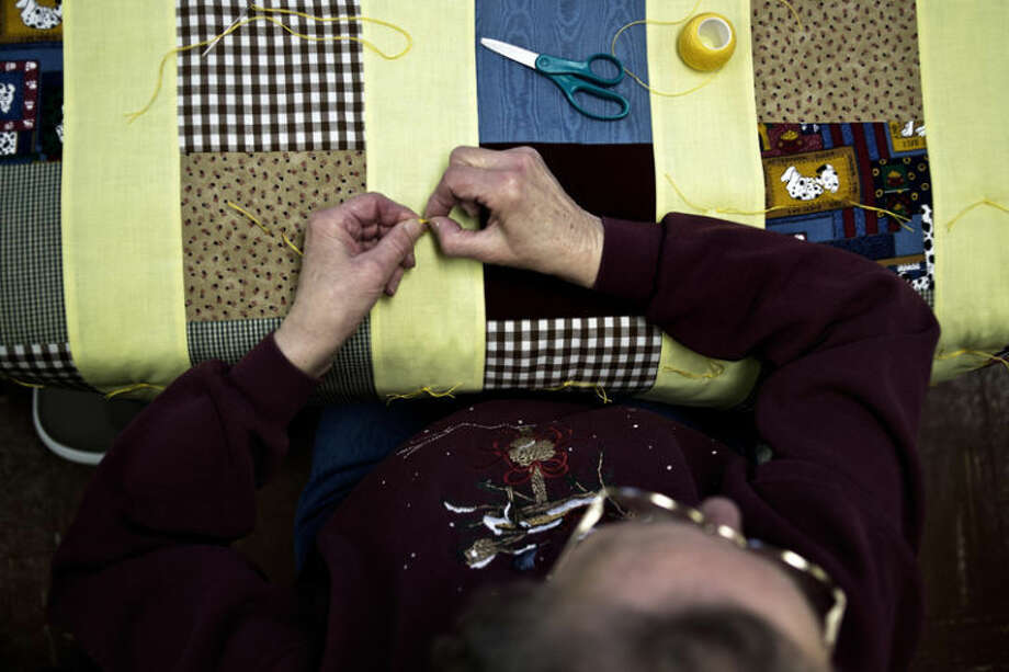 Carol Westphal, of Midland, works on tying a quilt during a meeting for Midland Quiltmakers at the Church of the Brethren. The group recently completed its 25,000th quilt. Photo: Sean Proctor/Midland Daily News