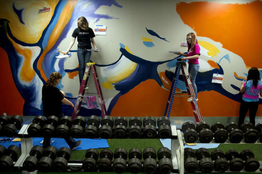 NEIL BLAKE | nblake@mdn.netBullock Creek senior Lynn Loubert, left, and junior Carolyn Ames work on step ladders as their art teacher Dana Murray walks underneath at Smitty's Iron Works in Midland on Tuesday. Photo: Neil Blake/Midland  Daily News