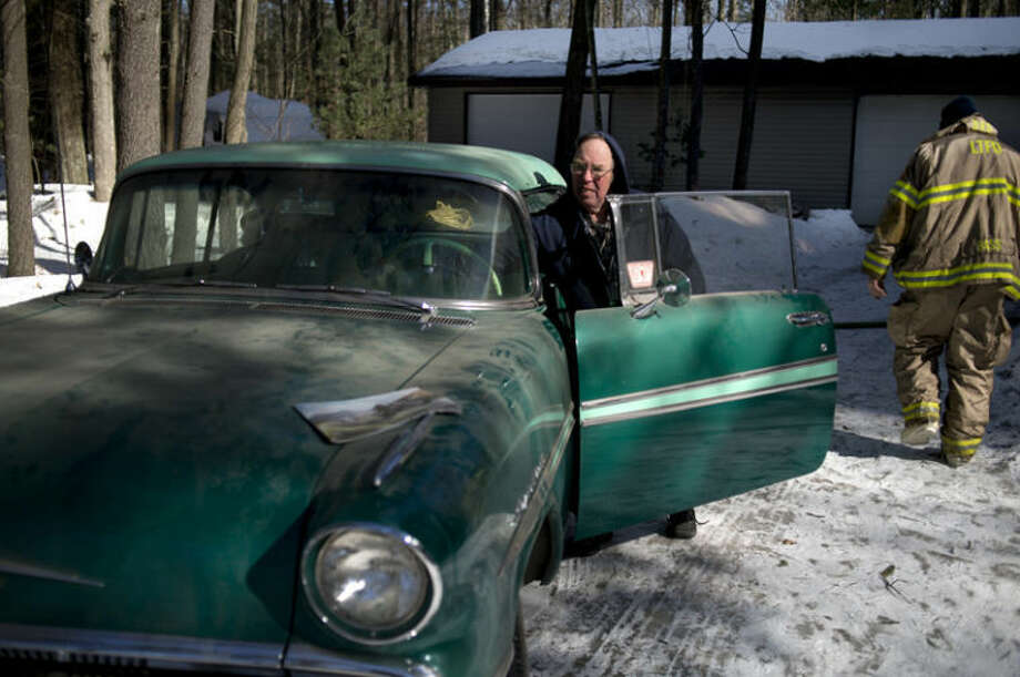"""Bud Smith prepares to move his 1957 Pontiac to safety away from his house, which was on fire Friday morning. Smith was working on remodeling a bathroom in the house when his girlfriend, Andrea Nartker, alerted him to flames creeping up the chimney. """"There was smoke real quick,"""" Smith said. Lee, Midland, Homer and Shepherd township fire departments all responded to the blaze."""