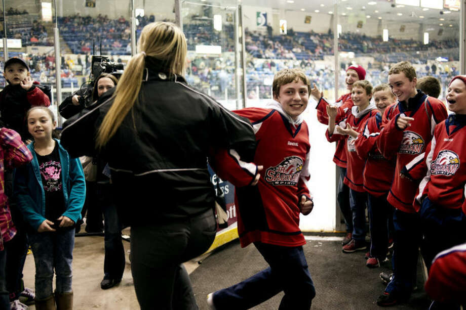Saginaw Spirit Game Day Promotions Intern Charley Porter dances with Dane Senkowski who was at the game with his team, the Junior Saginaw Spirit, at The Dow Event Center on Wednesday. The Spirit lost 7-3. Game 5 is scheduled for 7:11 p.m. Thursday at The Dow Event Center. Photo: Neil Blake/Midland Daily News