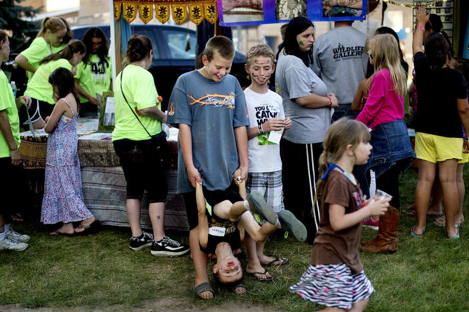 Jacob Wirtz, 11, flips Michael Brown, 6, over as Brown's brother Braiden, 11, right, looks during the West Midland Family Center 40th anniversary celebration. Activities included swimming, music, archery tag, petting zoo, climbing wall, relay races and more. Photo: NICK KING | Nking@mdn.net