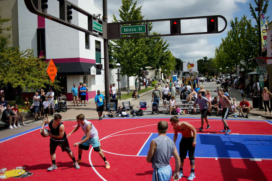 Two teams battle at the intersection of Main and McDonald streets during the Gus Macker basketball tournament on Sunday. Photo: NICK KING | Nking@mdn.net