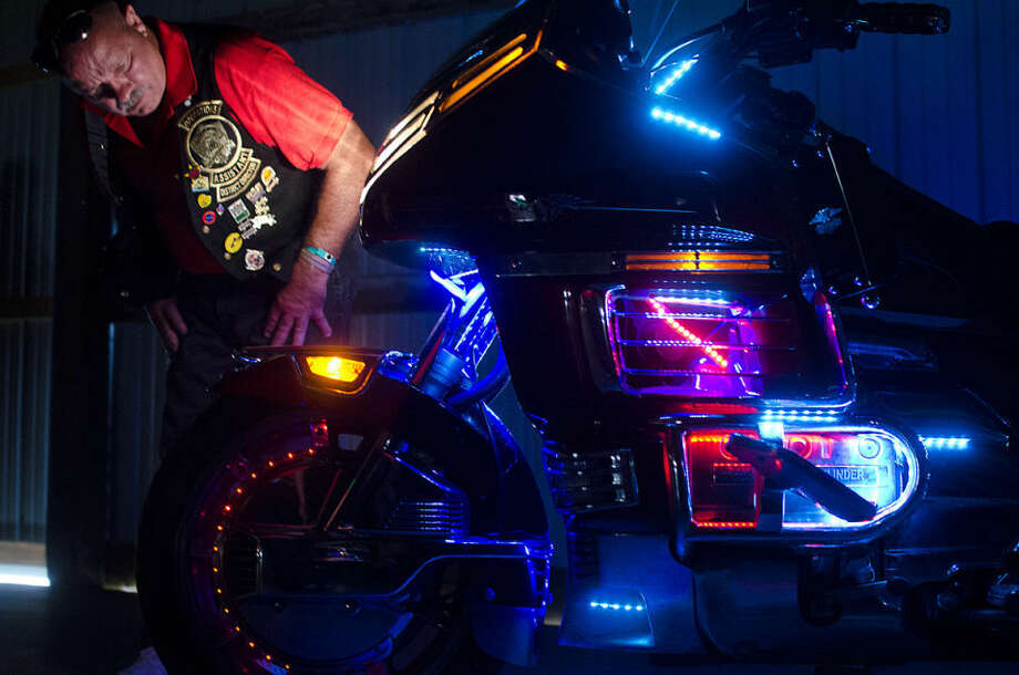"""Jim Lust of Crestline, Ohio, examines a motorcycle owned by K.C. Glad of Temperance during a light competition at the Gold Wing Road Riders Association Rally at the Midland County Fairgrounds on Saturday. Glad said the bike has about 2,000 lights on it, and he adds a little more each year. """"I get a lot of looks off it,"""" he said. """"Kids love it."""" Photo: Danielle McGrew 