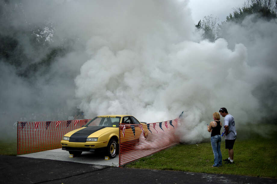 Rick Wendt performs a burnout in his Chevy Beretta as Bill Oswald, right, and his daughter Sarah keep time during the Hot Rods and Hogs car, truck and bike show on Sunday at the Sanford American Legion. Photo: NICK KING | Nking@mdn.net