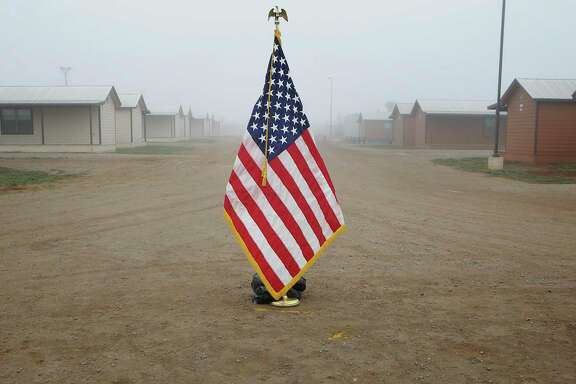 "An American flag is set in the middle of the pathway, where Secretary of Homeland Security Jeh Johnson toured the new South Texas Family Residential Center, just outside Dilley, Texas.  Detained immigrants that are currently being held in Artesia will begin arriving at the Dilley facility within the next two weeks.  This pictured center, built as a ""man camp"" for the oil and gas industry, is a temporary center that will be used until the new facility is completed. The new facility will accomadate 2400 individuals. Monday, Dec. 15, 2014."