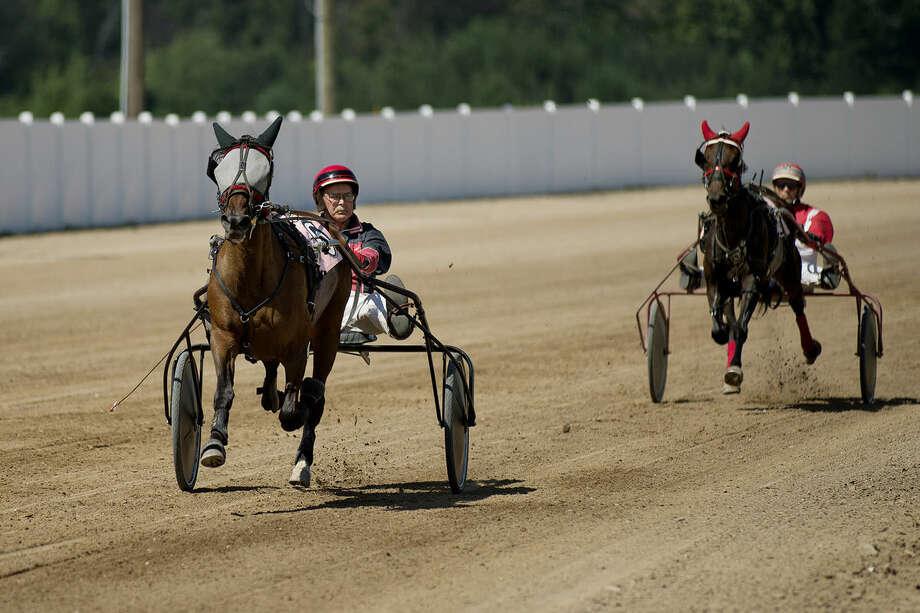 Racer Marshall Makin, left, rides PT Kaye across the finish line to win the first one mile trot race on Sunday during the harness racing event at the Midland County Fairgrounds. Racer Tim Driver, riding Moose Prints, right, finished second. Photo: NICK KING | Nking@mdn.net