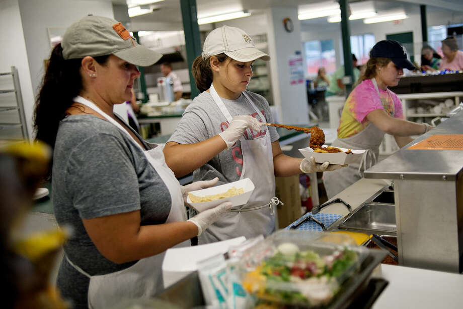 Sara Spangler, left, looks on as her daughter, Aliyah, 11, center, prepares nachos for a customer at the 4-H Cafeteria on Monday at the Midland County Fair. Aliyah and Jessica McNeal, right, 18, are members of the Rainbow Riders 4-H group. Photo: NICK KING | Nking@mdn.net