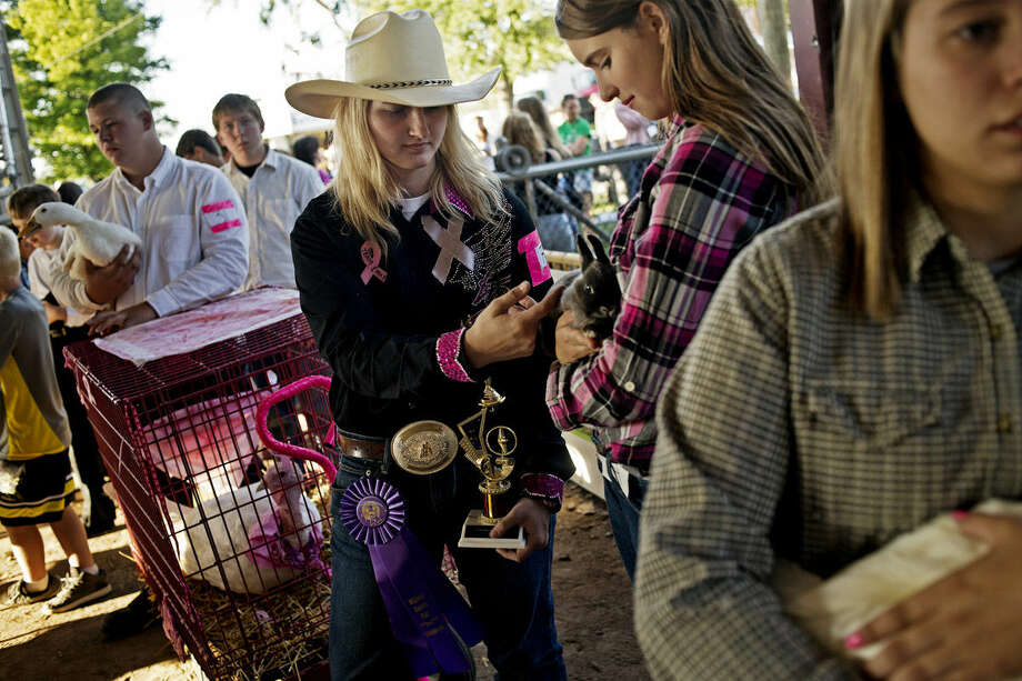 """Megan Mathews, 16, of Midland, waits to sell her turkey, Miracle Ozzy, during the Small Animal Auction on Wednesday at the Midland County Fair. For the past two years Mathews has donated 100 percent of her proceeds to breast cancer awareness and research, after her best friend died of cancer. """"One of my goals in life is to find a cure for cancer,"""" she said. Photo: SEAN PROCTOR   Sproctor@mdn.net"""
