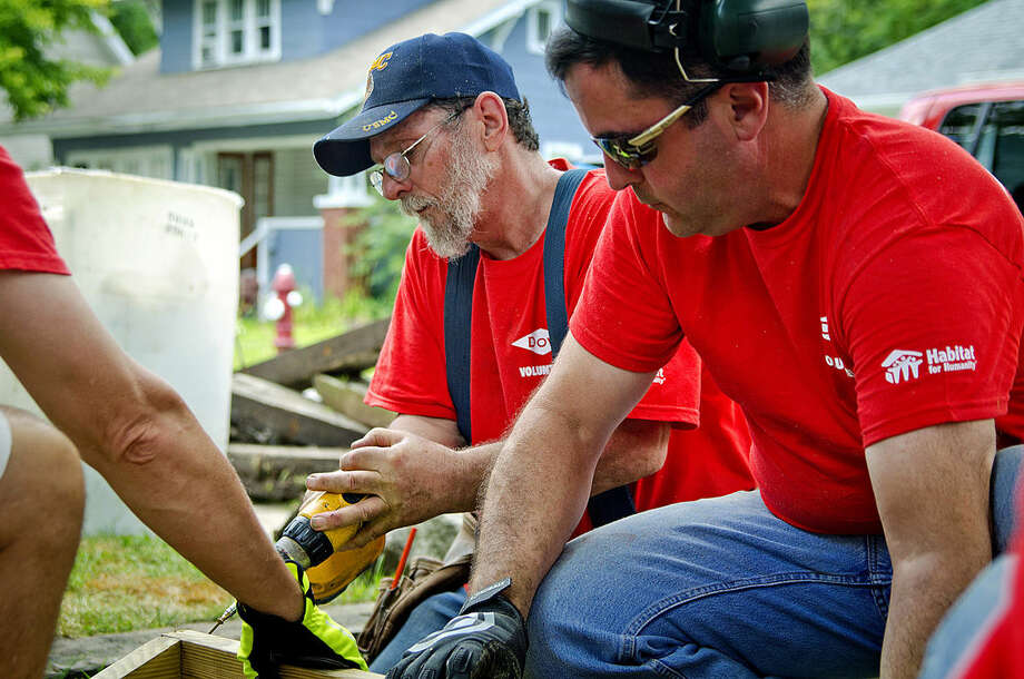 "Earl Denomme, left, screws together pieces of a new stairway for the porch of his Sayre Street home with the help of Dominic Zoeller and other volunteers for the Midland County Habitat for Humanity's Neighborhood Revitalization Initiative. Denomme said he has volunteered with Habitat for about 15 years and is grateful for the opportunity to work on his own home. ""What goes around did come around (for him)"" said fellow volunteer Bob Brentin. Photo: Danielle McGrew 
