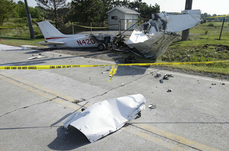 The wreckage from a plane that crashed rests on the side of a road Tuesday, in Richmond Heights, Ohio. The Cessna 172R crashed and burst into flames just after takeoff Monday from Cuyahoga County Airport in Richmond Heights, Ohio, outside of Cleveland, killing all four people on board, according to the Ohio State Highway Patrol. Photo:  (AP Photo/Tony Dejak)