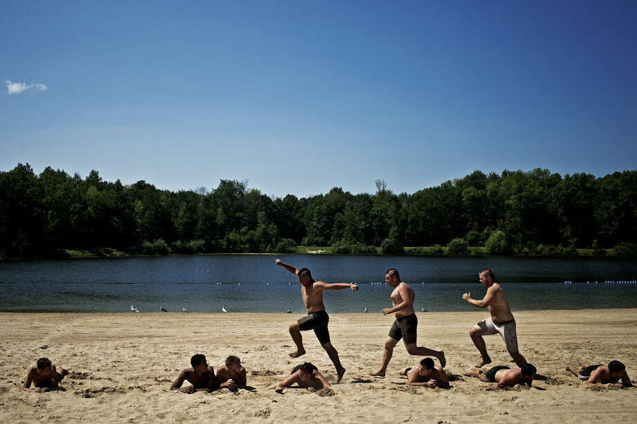 "Members of the Saginaw Nouvel Catholic Central varsity football team do workouts on the beach at Stratford Woods Park Thursday afternoon on their way back down from Camp Oak Hills in Harrison. For the past four years the team has been going there for conditioning training before the start of two-a-days, and always stop at Stratford for a final workout followed by pizza and swimming. ""It gives the team a chance to bond in fellowship and faith,"" defensive coordinator Greg Meter said. Photo: Sean Proctor/Midland Daily News"