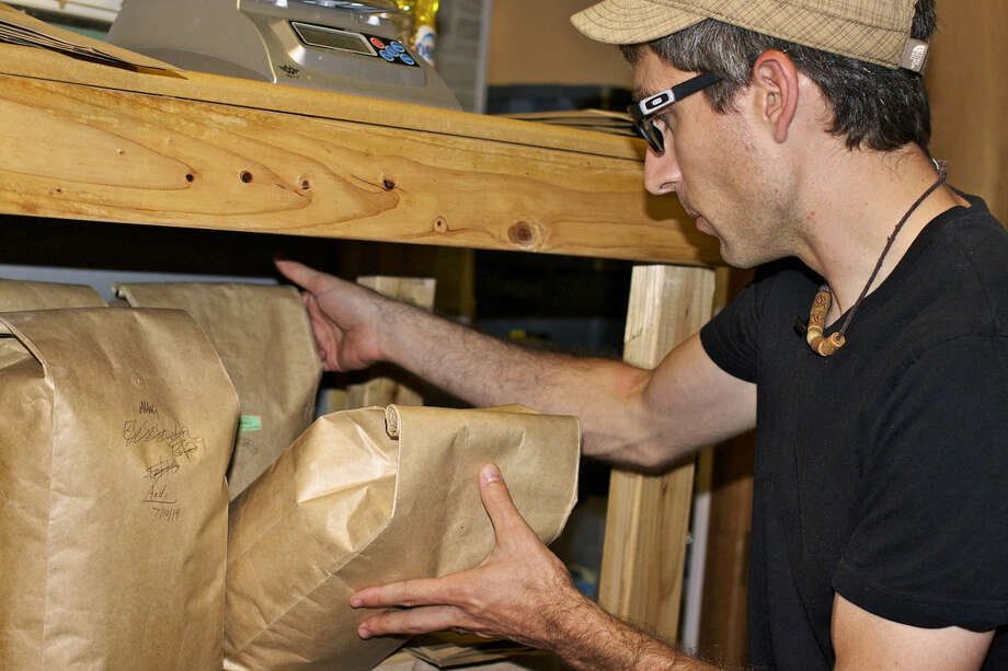 Aaron Cromar shuffles paper bags full of his roasted beans to locate the varieties he'll serve at market the next day. Photo: Mark Fairbrother | For The Daily News