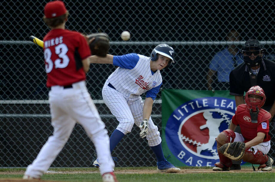 Northeast's Jacob Stone, center, hits the ball right back at the Canfield pitcher, Brandon Mikos, left, during the fourth inning Sunday at Ferguson Field in Indianapolis. Stone made it safely to first base. Canfield beat Northeast 8-1. Photo: NICK KING   Nking@mdn.net