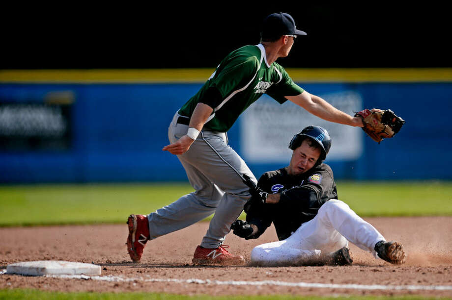 Sanford's Luke Anderson slides safely into third base around Adrian's Hunter Hayes Thursday during their game at Gerace Stadium at Northwood University. Photo: SEAN PROCTOR | Sproctor@mdn.net