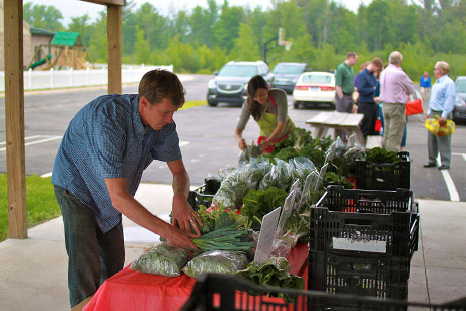 """Fred and Michele Monroe make final adjustments to one of two CSA pickup tables. This week's """"crate"""" included cilantro, leeks, Swiss chard, salad greens, kale, broccoli and more."""