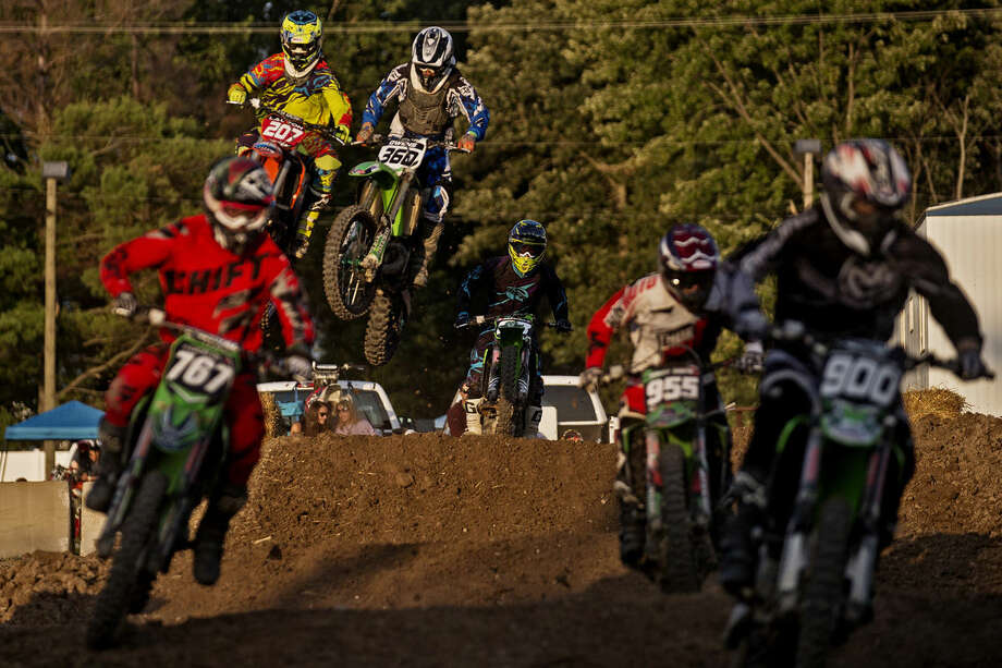 Racers take a straight away before coming to the first large jump Friday during the Super Cross event at the Midland County Fair. Photo: Sean Proctor/Midland Daily News