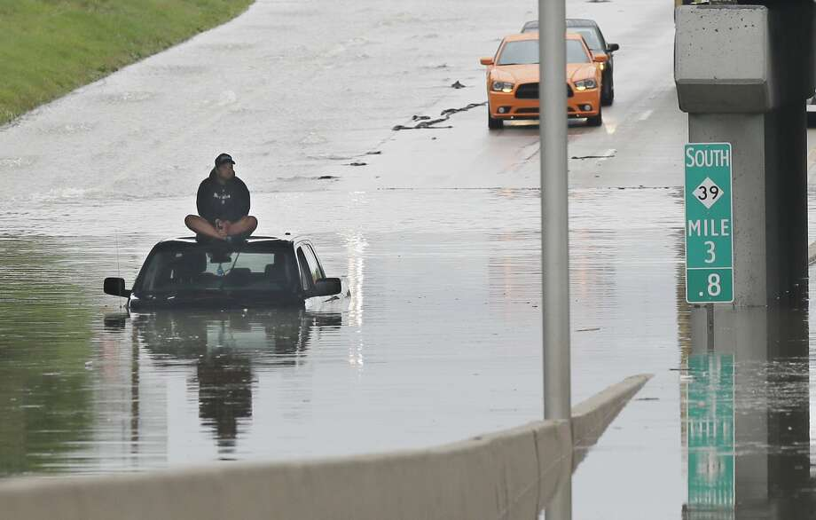 A stranded motorist sits on top his car as he awaits rescue from the flooded Southfield Freeway, Monday, Aug. 11, 2014, in Dearborn, Mich. The Michigan State Police issued an advisory Monday evening, urging drivers to avoid non-essential use of all metro Detroit freeways after heavy rain and thunderstorms left roads flooded and impassable. Interstate 75 at I-94 in Detroit has been shut down in both directions, according to the Michigan Department of Transportation. (AP Photo/Carlos Osorio) Photo: Carlos Osorio