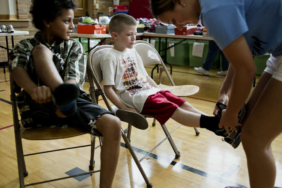 Jaydin Delong, 8, left, and Lukas Hall, 7, try on shoes as Gabrielle Rivette, a senior basketball player for Northwood University, checks the fit on Hall's shoes at SNEAKERPALOOZA at Carpenter Elementary School in Midland on Tuesday. Delong is entering the third grade at Carpenter and Hall is entering third grade at Meridian Elementary. Photo: NEIL BLAKE | Nblake@mdn.net