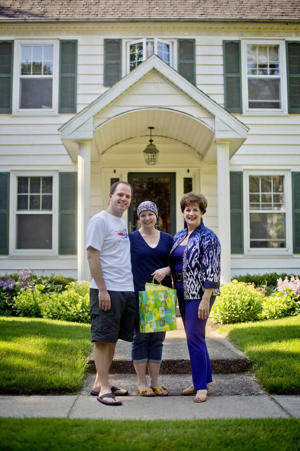 """Karin Beamer, right, gave engaged couple Matthew Christianson, left, and Rachael Sova a """"welcome to the neighborhood"""" gift bag. Photo: NICK KING   Nking@mdn.net"""
