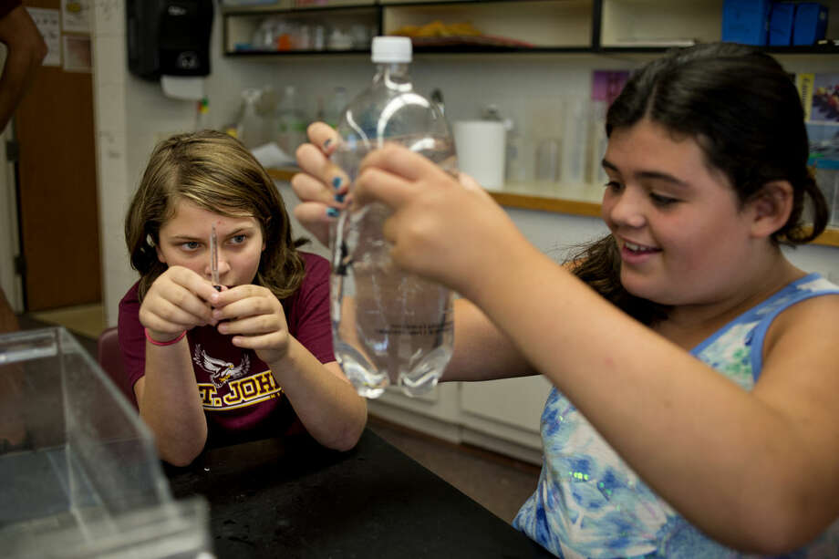 NEIL BLAKE | nblake@mdn.netGrace Binns, 11, left, and Danielle Browning, 11, apply pressure to their 2-liter bottle at the Summer Science Fun with H2O day camp at St. John's Lutheran School on Tuesday. The camp went from Monday through today and taught the campers about water-related science principles. Photo: Neil Blake/Midland Daily News