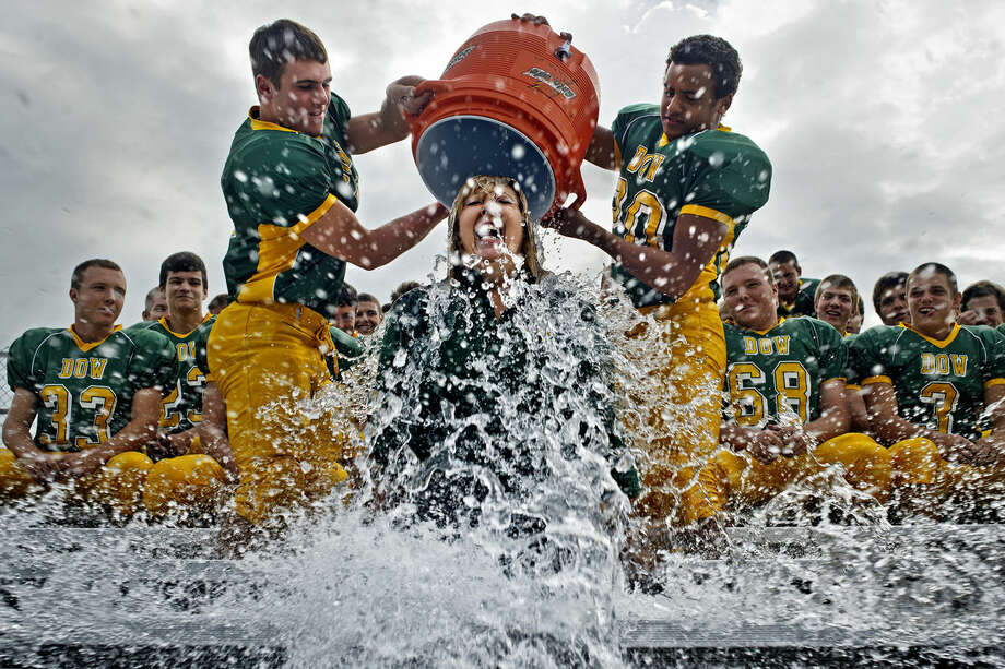 Dow High School's Principal Pam Kastl reacts as Dow varsity football players Connor Doyle, left, and Joey Lundahl dump ice cold water over her head while participating in the Ice Bucket Challenge last week during picture day for the varsity football team. Photo: SEAN PROCTOR   Sproctor@mdn.net