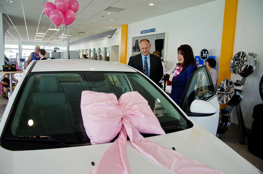Mary Kay Independent Sales Director Kim Loebig, right, of Midland, looks over her new Chevrolet Cruz. Photo: DANI MCGREW | For The Daily News