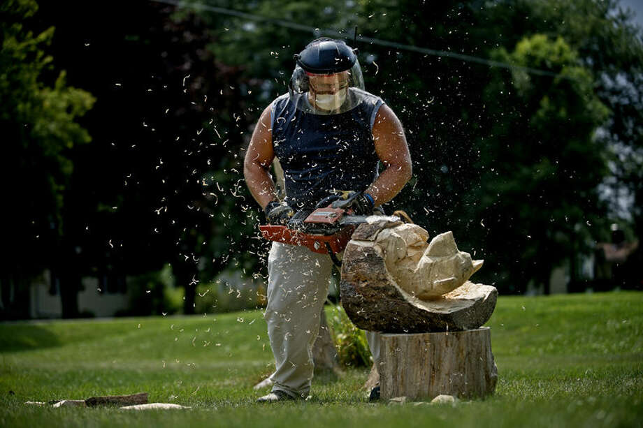"Tom Gillman, of Bay City, works on carving figures into the tree stumps outside of Lee and Linea Walkowski's hous. The Walkowskis originally got the idea for the carving after seeing similar work done in Mississippi following Hurricane Katrina. ""It was like beauty after disaster,"" Linea said. The stumps have been carved into bears, squirrels, owls, a woman and other figures. Photo: Sean Proctor"