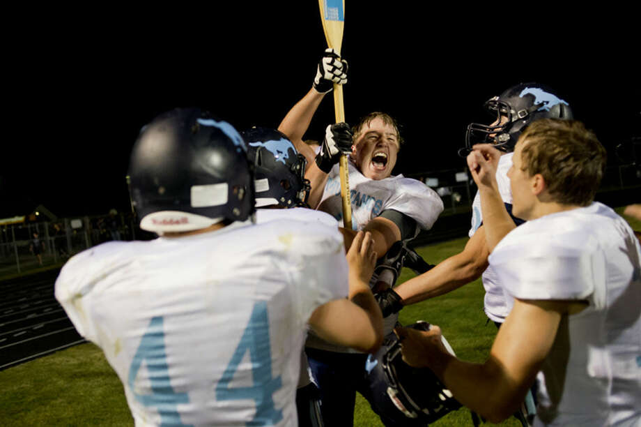 "NEIL BLAKE | nblake@mdn.net Meridian's Jess Levier hoists the infamous paddle after the annual ""Battle for the Paddle"" against Bullock Creek at Meridian High School on Thursday. The Mustangs won 36-20. Photo: NEIL BLAKE 