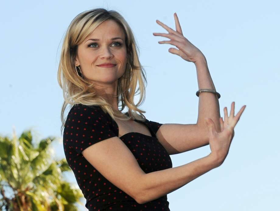 """Academy Award winning actress Reese Witherspoon (C) gestures at the ceremony to unveil her Hollywood Walk of Fame star in Hollywood on December 1, 2010.  Witherspoon grew up in Tennessee and returned to her roots to play June Carter Cash in the musical biopic, """"Walk the Line"""". Her performance earned her the 2005 Academy Award for Best Actress, the BAFTA, the Golden Globe, the Screen Actors Guild Award, the New York Film Critics Award, and many other honors. Photo: MARK RALSTON, AFP/Getty Images"""
