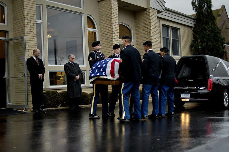 A U.S. Army honor guard carries the casket of Sgt. 1st Class Michael Cathcart into the Gephart Funeral Home on Monday in Bay City. Photo: NICK KING | Nking@mdn.net