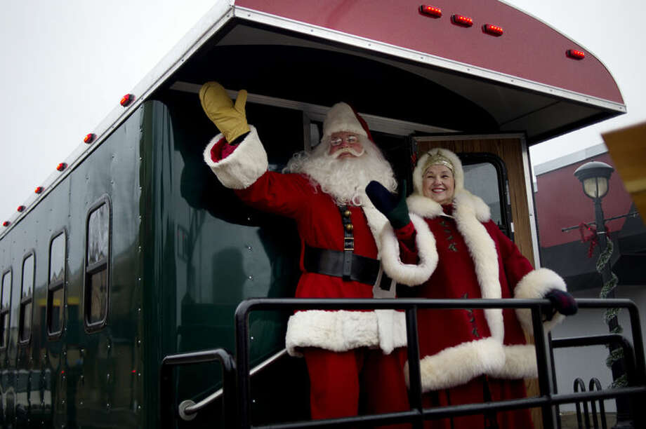 Santa and Mrs. Claus, on the Northern Star train, wave to parade attendees during the Santa Parade on Saturday in downtown Midland. Photo: Nick King/Midland  Daily News