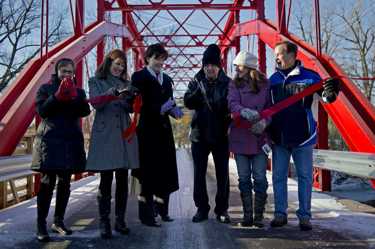 Mayor Maureen Donker, left, Attorney General Bill Schuette, right, were on hand Friday for the ribbon cutting ceremony for the newly renovated Currie Parkway bridge.