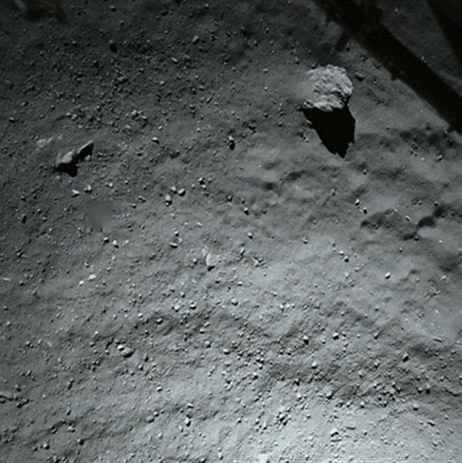 This image released by the European Space Agency ESA Thursday Nov. 13, 2014 was taken by Philae's down-looking descent ROLIS imager when it was about 40 meters (131 feet) above the surface of Comet 67P/Churyumov-Gerasimenko Wednesday. It shows that the surface of the comet is covered by dust and debris ranging from mm to metre sizes The large block in the top right corner is 5 m in size. In the same corner the structure of the Philae landing gear is visible. The lander scored a historic first Wednesday, touching down on comet 67P/Churyumov-Gerasimenko after a decade-long, 6.4 billion-kilometer (4 billion-mile) journey through space aboard its mother ship, Rosetta. The comet is streaking through space at 41,000 mph (66,000 kph) some 311 million miles (500 million kilometers) from Earth. (AP Photo/Esa,Rosetta,Philae) Photo: HONS