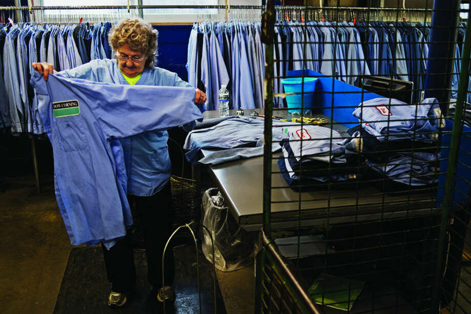 Dorothy Spangler folds clean shirts at Cintas. Photo: Sean Proctor