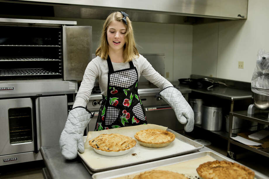 Erica Clark, 19, of Midland, pulls freshly baked pies from the oven at Trinity Lutheran Church on Wednesday before a worship service for the community at the church. Clark helped out while on Thanksgiving break from Grand Valley State University. Photo: NEIL BLAKE | Nblake@mdn.net