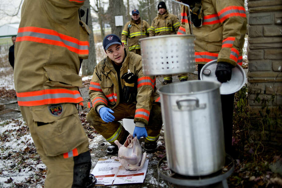 Midland firefighter Jason Schumer, center, picks up a thawed turkey before placing it in a fryer during a demonstration about the proper and improper way to deep fry a turkey on Monday at a training house off Rockwell Drive in Midland. Photo: NICK KING | Nking@mdn.net