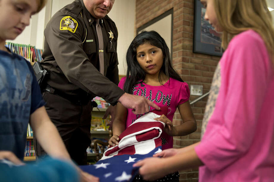 Adams fourth grader KenNiya Valentine looks up while getting folding instructions from Midland County Sheriff Scott Stephenson at the school on Thursday. Stephenson and Brad Blanchard put on a program about flag etiquette at area elementary schools to raise awareness about how to honor Old Glory. Blanchard is with the Veteran's Outreach at the Dow Chemical Company. Photo: Neil Blake/Midland Daily News