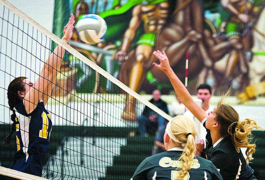 Standish-Sterling sophomore Stephanie Steinbauer tries to block a hit from Bullock Creek sophomore Paige Dopp during the first round of the district tournament at Pinconning High School on Monday. Bullock Creek beat Standish-Sterling 25-17, 25-12 and 25-16 and will play against John Glenn on Wednesday. Photo: Danielle McGrew   For The Daily News