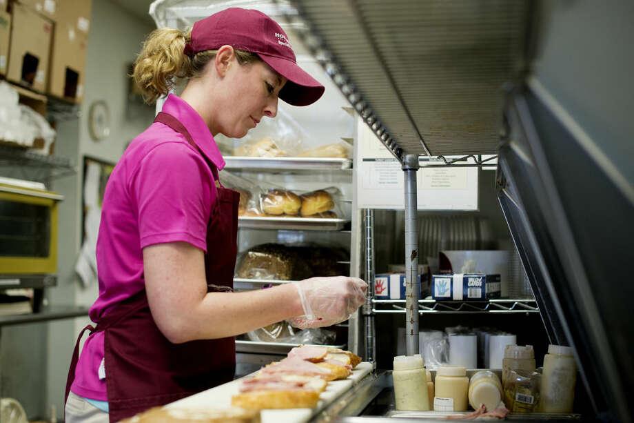 Kristen Komara demonstrates how to make a signature sandwich at Honeybaked Ham in Midland. Photo: NEIL BLAKE | Nblake@mdn.net