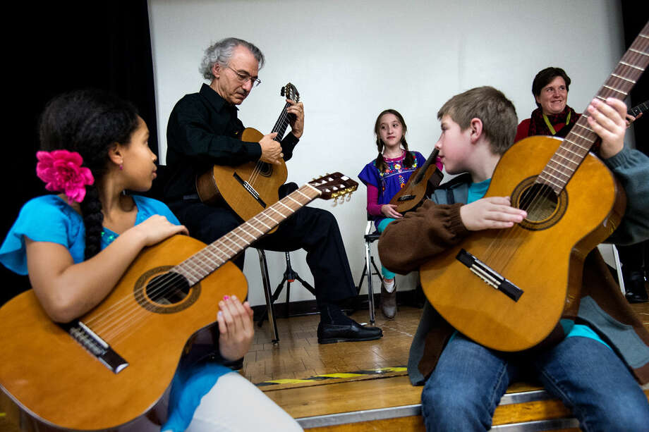 Angelo Cassar, of Midland, instructs students on traditional flamenco music during Midland Public School's fifth grade Fiesta Hispana at Central Middle School on Friday night. Cassar owns a guitar studio in his Midland home, and performed a traditional flamenco song in the gymnasium later that night. Photo: ZACK WITTMAN | For The Daily News