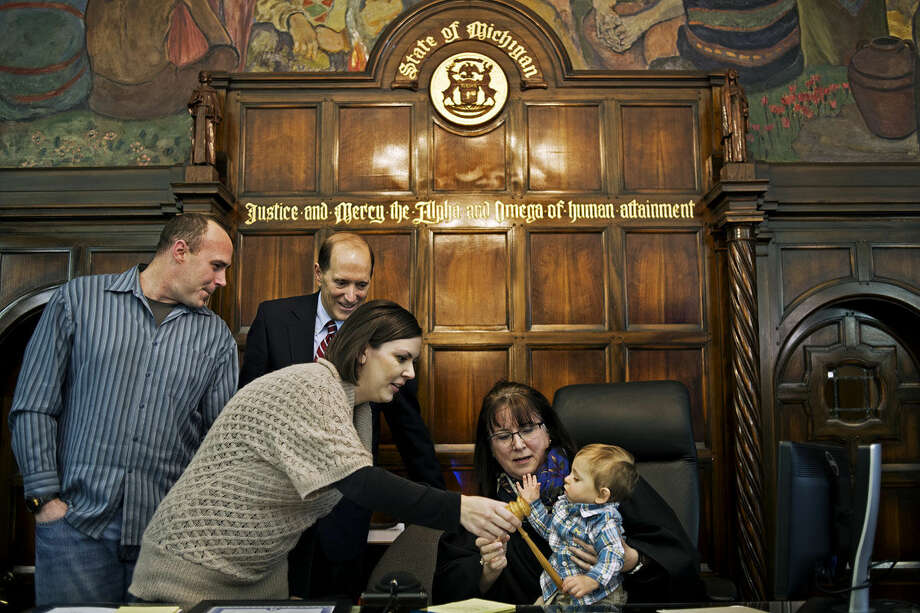 Sara Letson helps Judge Dorene Allen hand Letson's newly adopted son, Blake, the gavel to officially close his case on Tuesday morning during Adoption Day at the Midland County Courthouse. U.S. Congressman Dave Camp was in attendance. Photo: SEAN PROCTOR | Sproctor@mdn.net