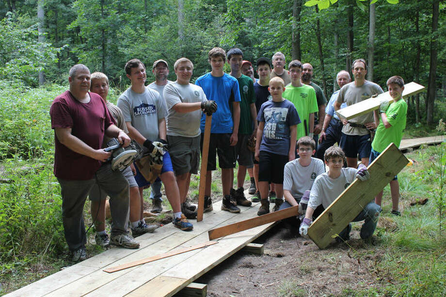 Eagle Scout candidate Matthew Pawley and his volunteers stand on the 170-foot section of boardwalk they built at Forestview Natural Area. The boardwalk leads visitors through a large wetland area on the property. Photo: Photo Provided