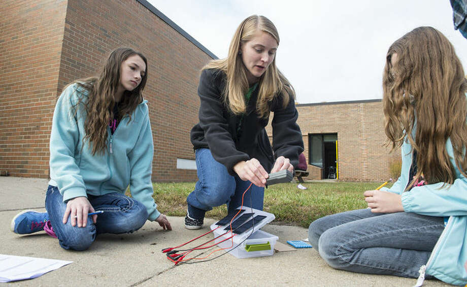 Bullock Creek Middle School teacher Ashley Meyer, center, shows students Tiana Lowery, left, and Veronica Card how to measure the energy generated by solar panels. Photo: Photo Provided