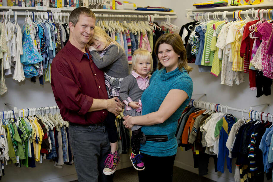 Ty Hammond and Constance Starks hold their daughters, Gracie, 5, and Leah, 1, at their store, the Children's Jungle in Midland. Photo: Neil Blake/Midland Daily News