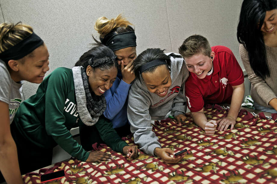 From left, Deviree Denson, Mercedez Willis, Dymond Perry, Champagne Arthur, Destiny Soulliere and Emily Balcueva, all members of the Delta College women's basketball team, laugh at a snapshot while making a blanket Friday during the second annual Kids Blanket-Making Party at Delta College. Photo: SEAN PROCTOR | Sproctor@mdn.net