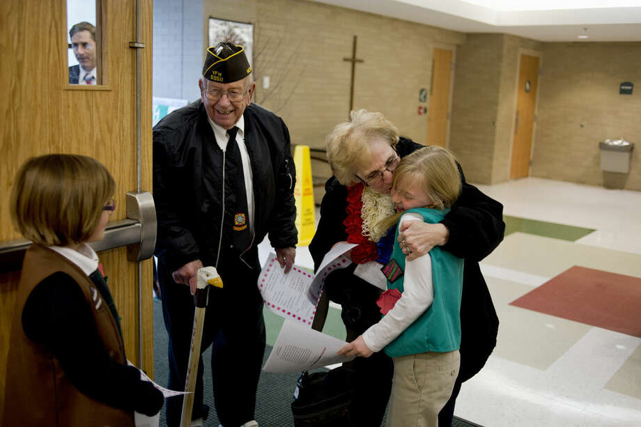 St. Brigid fourth grader Raegan Woodiwiss hugs her grandmother, Grace Chevalier, as she and her husband, Al, arrive for a Veterans Day Celebration at St. Brigid on Tuesday. Al Woodiwiss served in the Navy during the Korean War. The program included music from the Shamrock Band and remarks from State Sen.-elect Jim Stamas. Photo: Neil Blake/Midland Daily News