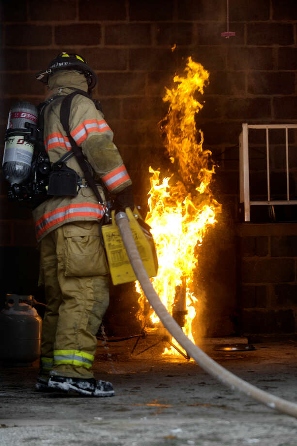 Midland firefighter Jason Schumer puts out a deep frier fire Monday at a training house off Rockwell Drive. Photo: Nick King | Nking@mdn.net
